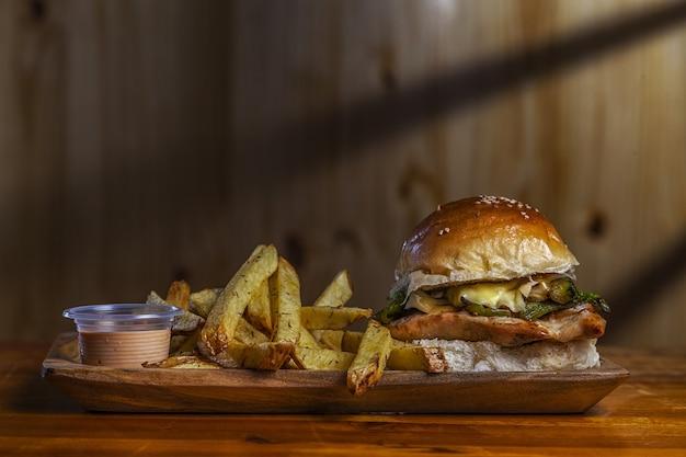 Close-up shot van een heerlijke hamburger met frietjes op tafel
