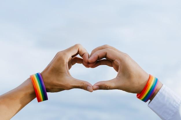 Close-up shot van een homopaar hand in hand met een regenboog polsbandje gemaakt handen die een hartvorm vormen
