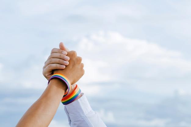 Close-up shot van een homopaar hand in hand met een regenboogpolsband in de lucht
