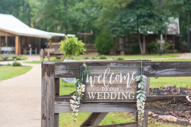 Close-up shot van een houten hek met de tekst 'welkom op onze bruiloft'