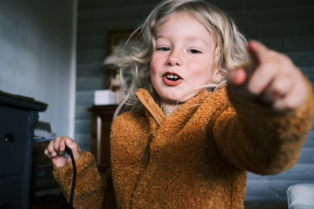 Close-up shot van een jong blond meisje dat een bruine winterjas draagt