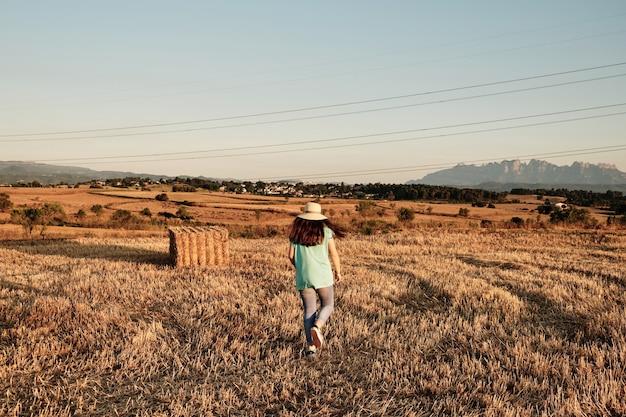 Close-up shot van een jong meisje met een ronde hoed die in het veld loopt