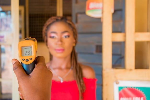 Close-up shot van een jonge afrikaanse vrouw die een infrarood voorhoofdthermometer (thermometerpistool) gebruikt om haar lichaamstemperatuur te controleren op virussymptomen - concept van epidemische virusuitbraak