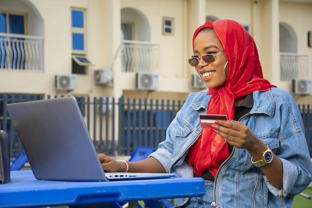 Close-up shot van een jonge afro-amerikaanse vrouw die lacht terwijl ze haar laptop en creditcard gebruikt