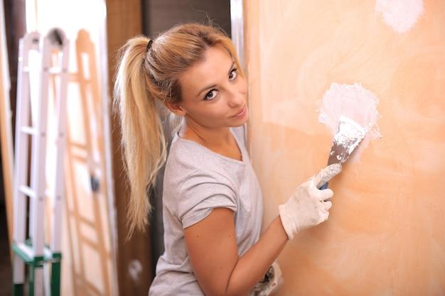 Close-up shot van een jonge blonde vrouw puttying de muur onder de lichten - interieur concept