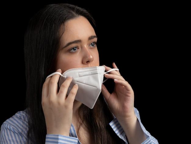 Close-up shot van een jonge vrouw die een beschermend medisch masker opzet
