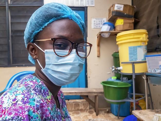 Close-up shot van een jonge zwarte vrouw met een haarnetje en een medisch gezichtsmasker