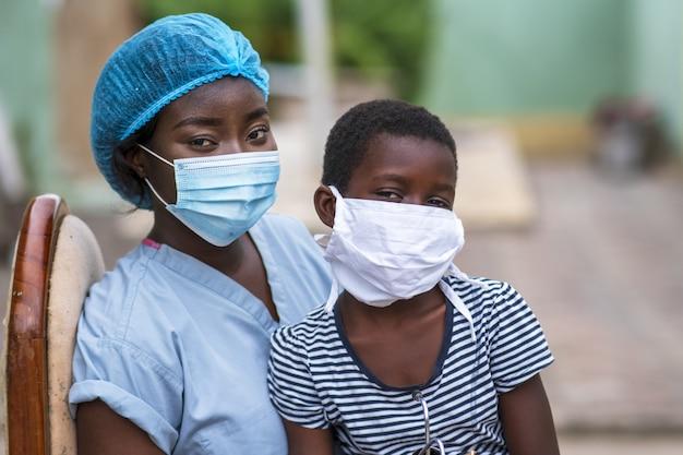 Close-up shot van een jongen en een dokter die hygiënische maskers dragen