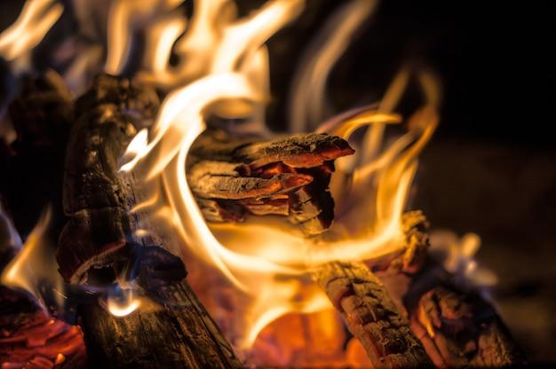 Close-up shot van een kampvuur met brandend hout en een open vlam 's nachts