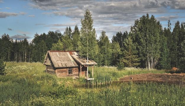 Close-up shot van een klein huis in de buurt van een vijver op het platteland