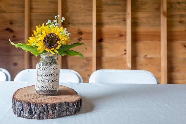 Close-up shot van een kleine vaas met prachtige zonnebloemen op een stuk van een houten stam