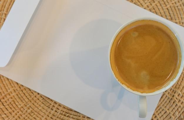 Close-up shot van een koffiemok geplaatst op een witte envelop, bovenaanzicht shot.