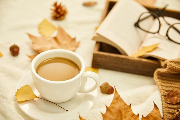 Close-up shot van een kopje koffie en herfstbladeren op houten oppervlak