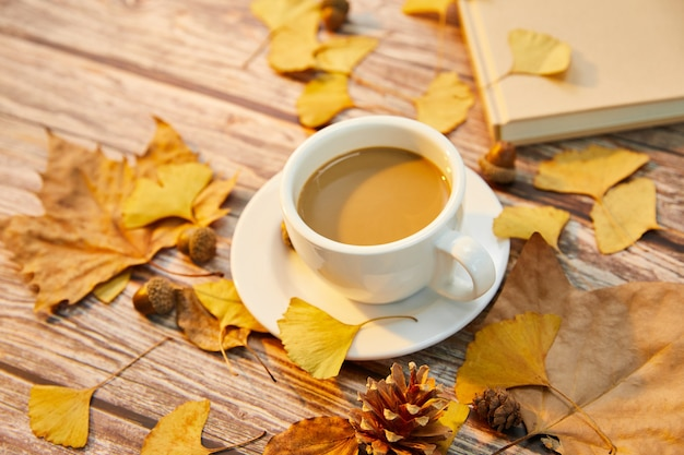 Close-up shot van een kopje koffie en herfstbladeren