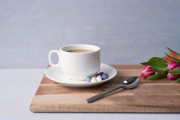 Close-up shot van een kopje warme koffie met melk op het bord in de buurt van een bloemboeket onder de lichten