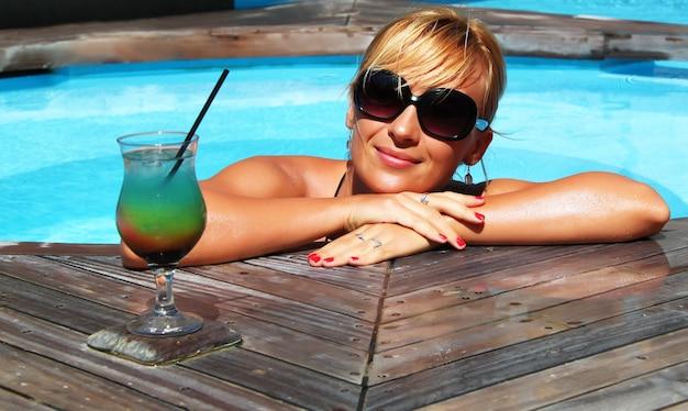 Close-up shot van een lachende blonde vrouw met een kopje sap in het zwembad
