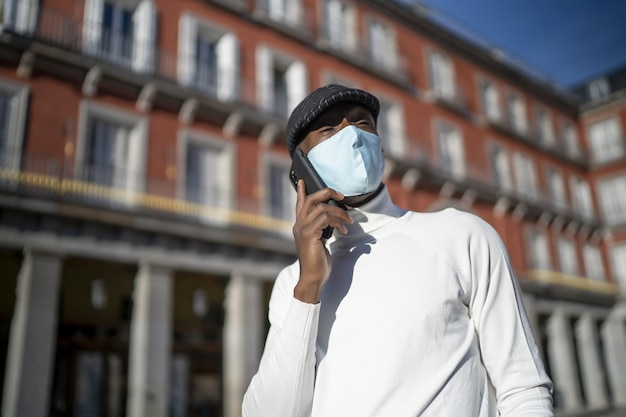 Close-up shot van een man die aan de telefoon praat en een coltrui draagt