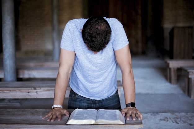 Close-up shot van een man die de bijbel op een houten tafel leest