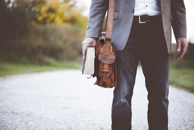 Close-up shot van een man die een pak draagt en staat terwijl hij de bijbel vasthoudt