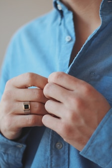 Close-up shot van een man in een formele outfit met een gouden ring