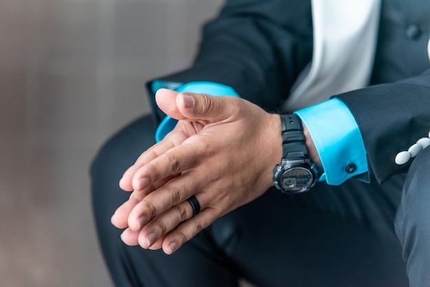 Close-up shot van een man in een pak die zijn handen bij elkaar houdt tijdens het wachten