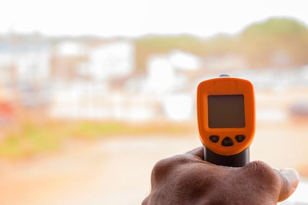 Close-up shot van een man klaar om infrarood voorhoofdthermometer (thermometerpistool) te gebruiken om de lichaamstemperatuur te controleren op virussymptomen - concept van epidemische virusuitbraak