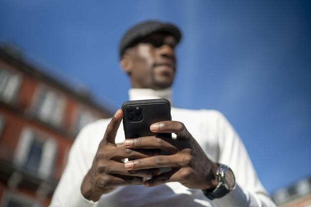 Close-up shot van een man met een coltrui en een hoed die zijn telefoon vasthoudt