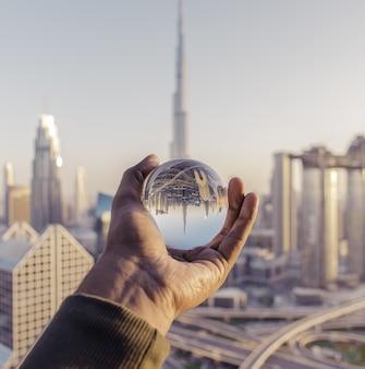 Close-up shot van een mannelijke hand met een kristallen bol met de weerspiegeling van de stad