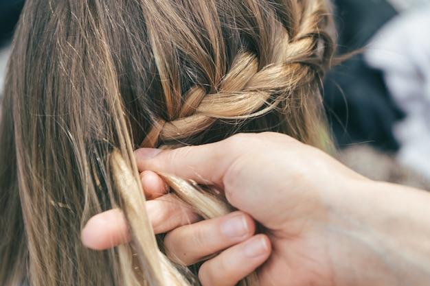 Close-up shot van een meisje dat haar vlechten krijgt