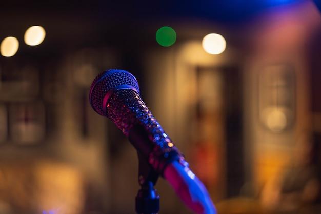 Close-up shot van een microfoon op een wazige ruimte met bokeh lichten