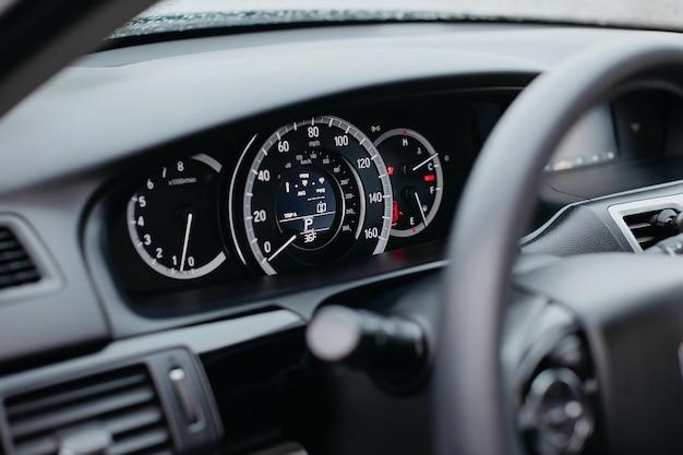 Close-up shot van een mijl snelheidsmeter in een auto. autodashboard. dashboarddetails met indicatielampjes. auto-instrumentenpaneel. dashboard met snelheidsmeter, toerenteller, kilometerteller.