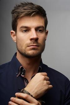 Close-up shot van een modieuze knappe man in een blauw klassiek shirt