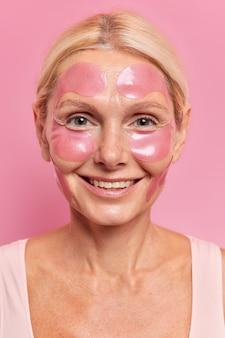 Close-up shot van een mooie volwassen oude vrouw brengt vochtinbrengende pleisters op het gezicht aan om fijne lijntjes te verminderen