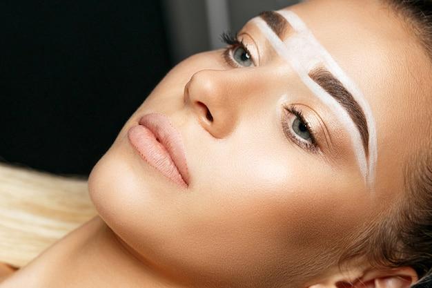 Close-up shot van een mooie vrouw met wenkbrauwpasta op haar wenkbrauwen voor permanente make-up