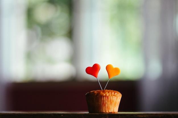 Close-up shot van een muffin met kleurrijke hartjes erop