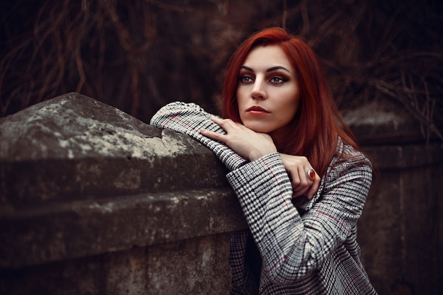 Close-up shot van een multiraciale vrouw die poseert terwijl ze leidt op de stenen muur