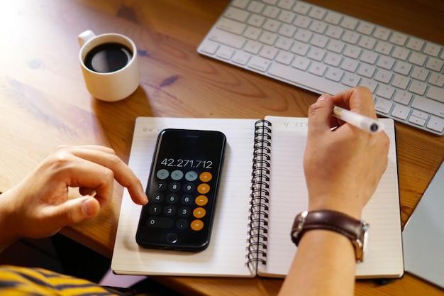 Close-up shot van een ondernemer die vanuit huis werkt en berekeningen doet