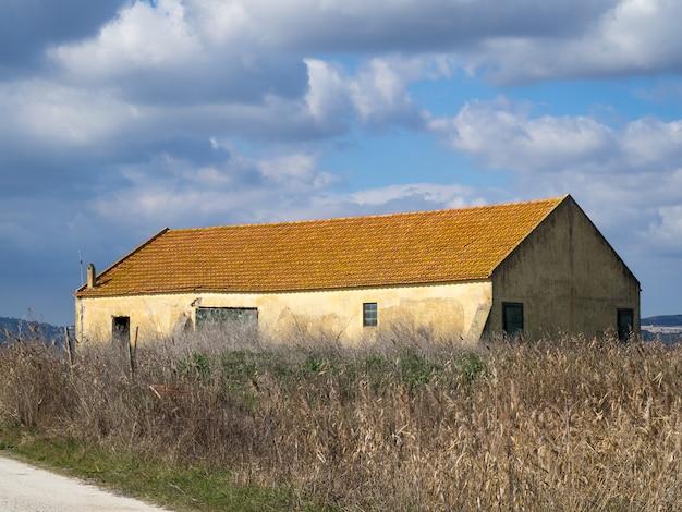 Close-up shot van een oude boerderij in een veld met witte en grijze wolken op de achtergrond