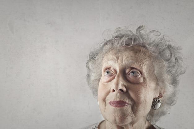 Close-up shot van een oude dame met blauwe ogen en grijs haar