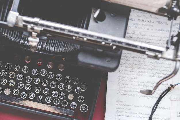 Close-up shot van een oude vintage typemachine op een rood bureau met papier aan de zijkant