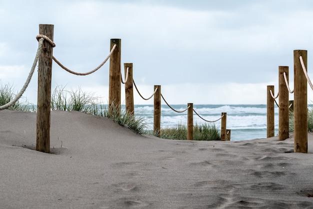 Close-up shot van een pad op het zandstrand dat naar de oceaan leidt