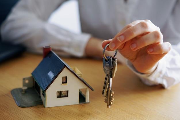 Close-up shot van een persoon die denkt aan het kopen of verkopen van een huis