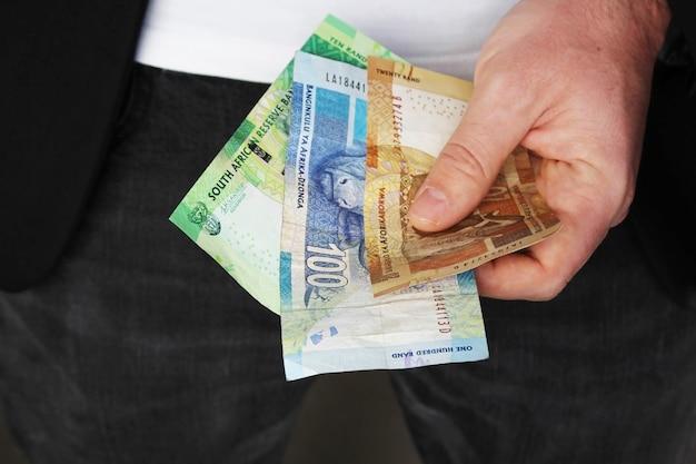Close-up shot van een persoon die een pak draagt en wat contant geld in zijn hand houdt