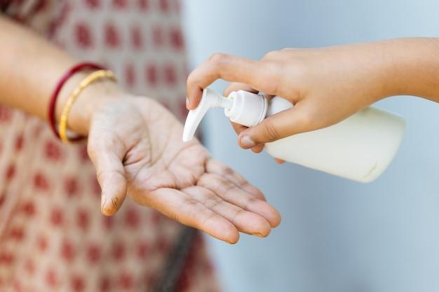 Close-up shot van een persoon die een vloeibare zeep op de hand van de vrouw giet
