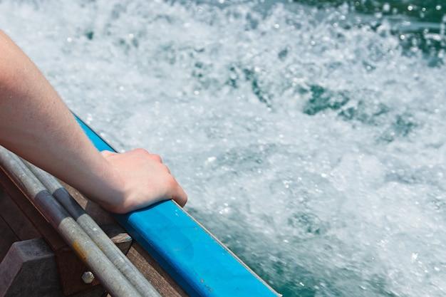 Close-up shot van een persoon die zijn hand op het schip op zee legt