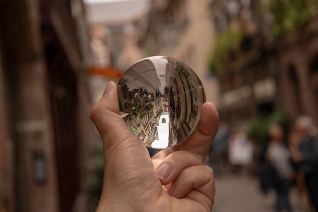 Close-up shot van een persoon met een kristallen bol met de weerspiegeling van historische gebouwen