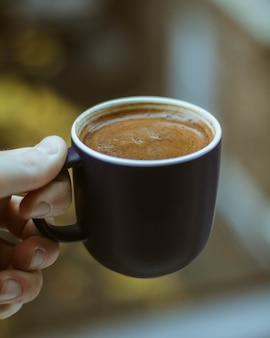 Close-up shot van een persoon met een zwarte kop koffie