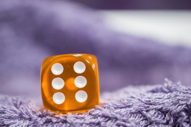 Close-up shot van een plastic oranje dobbelstenen met zes stippen op een zachte stof