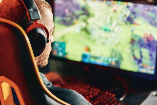 Close-up shot van een professionele mannelijke cybersport-gamer die een koptelefoon draagt die online videogame speelt