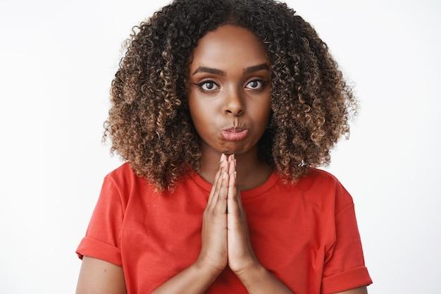 Close-up shot van een pruilende vrouw hand in hand in gebed en hoopvol naar voren kijkend als smekend om gunst of vergeving, somber overstuur gezicht makend als medelijdend of schuldig verontschuldigend over witte muur